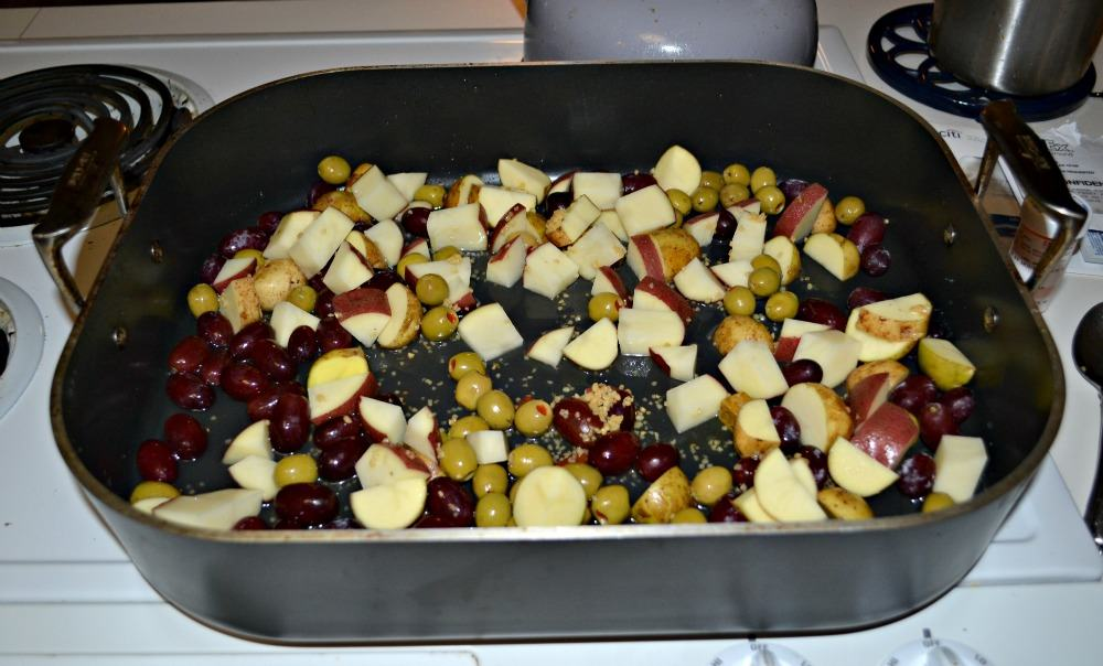 Potatoes, grapes, and olives ready for roasting with a whole chicken