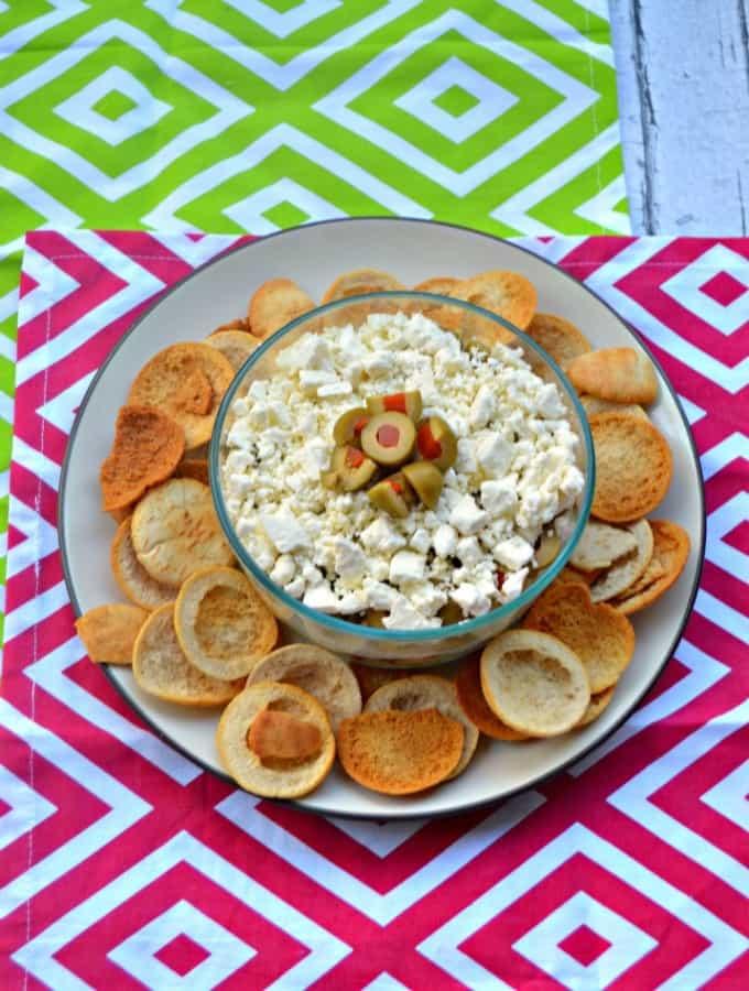 Mediterranean Layer Dip has layers of hummus, sun dried tomatoes, feta cheese, Mezzetta Olives, and artichokes!