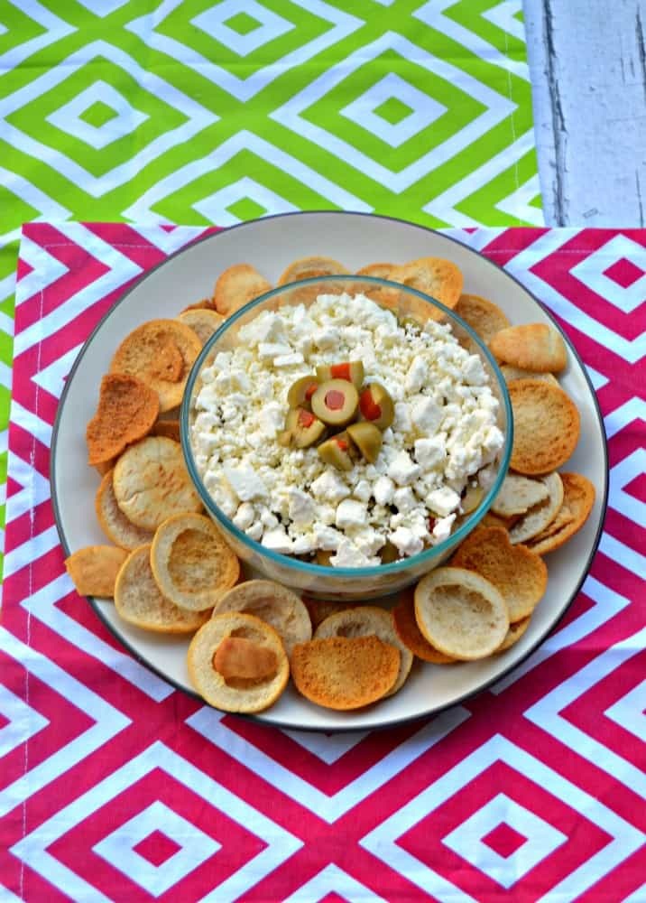 Mediterranean Layer Dip has layers of hummus, sun dried tomatoes, feta cheese, Mezzetta Olives, and artichokes!