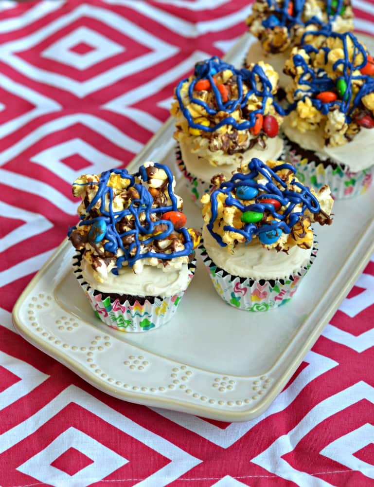 How fun would Movie Theater Cupcakes be for a movie night at home? Made with popcorn, chocolate candy, soda, and cake, these combine all your movie theater favorites.