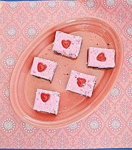 A pink platter with five pieces of Double Layer Double Fudge with milk chocolate on the bottom and pink white chocolate on the top each one with a heart on it on a pink background.