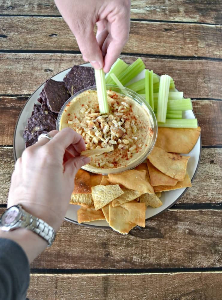 Make your hummus something special by topping it with ginger and walnuts and served with chips and veggies