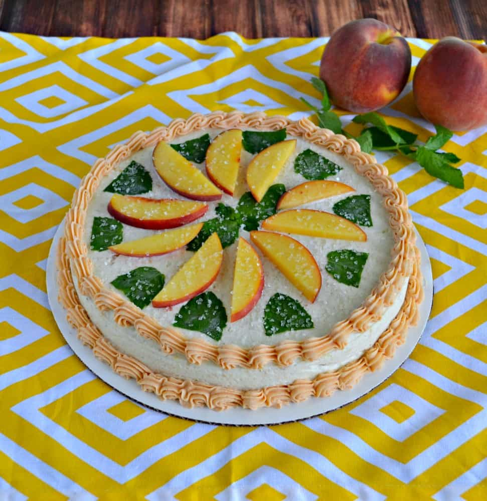 Brown Butter and Peach Chardonnay Ice Cream Cake topped with Chardonnay Buttercream, fresh mint, and peaches! It's all made with The Curious Creamery Sweet Cream Ice Cream Cake mix