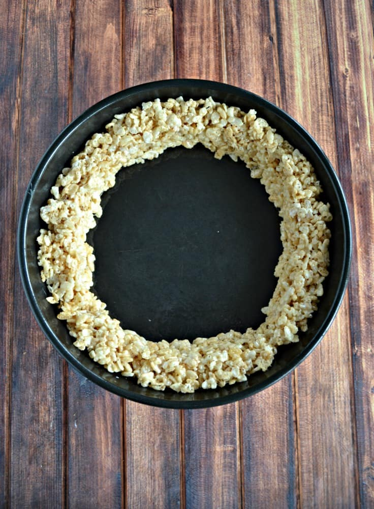 "Making the ""crust"" of this fun Pumpkin Pie Rice Krispies Treat!"