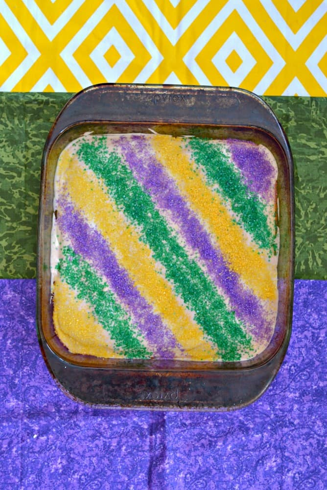 A layer of sugar cookie, and layer on cheesecake and a layer of sprinkles made these King Cake Cookie Bars sparkle!