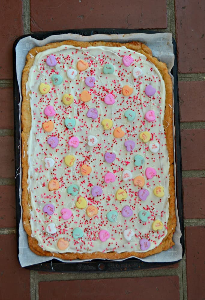 A layer of white chocolate, conversation hearts, and sprinkles makes this Sugar Cookie Bark perfect for Valentine's Day!
