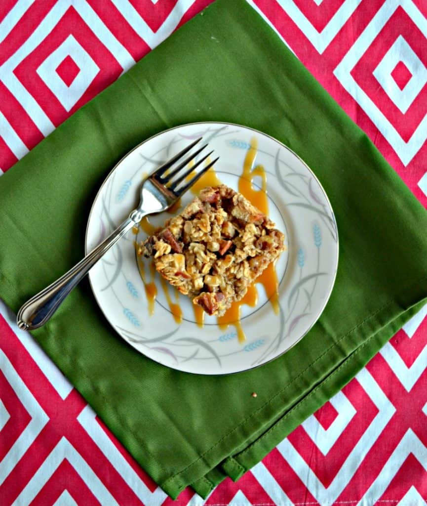 A white plate topped with an oatmeal square that is brown with apple pieces and has a caramel drizzle on top with a fork on the left side of the plate sitting on a green napkin on a red and white background.
