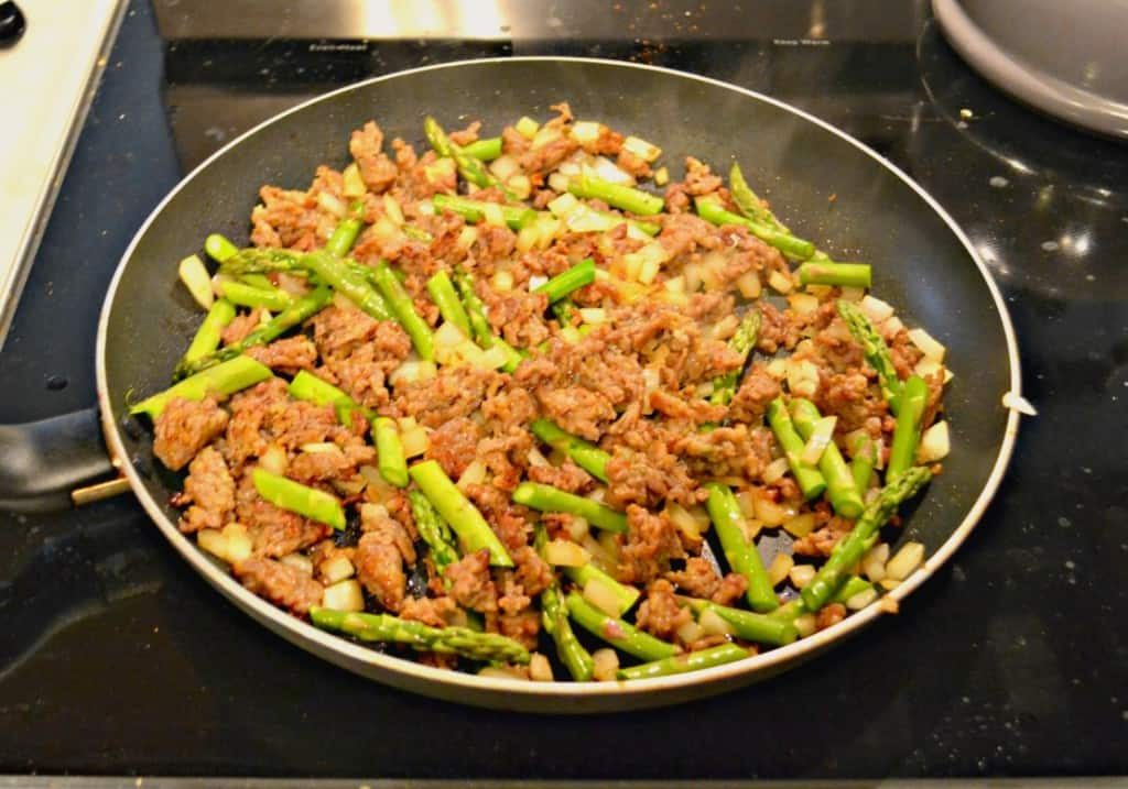 Saute sausage, asparagus, and onions for a delicious breakfast quiche
