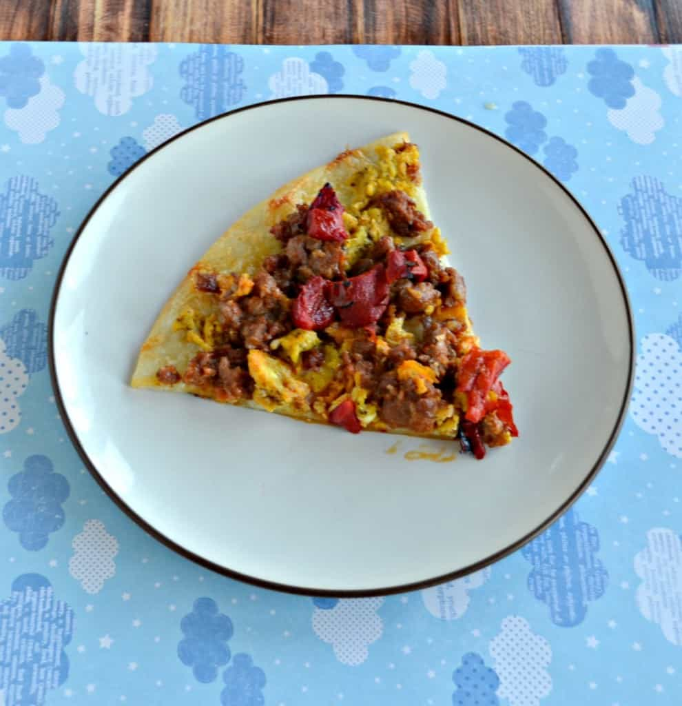 Breakfast Pizza topped with cheese, sausage, onions, peppers, and eggs.