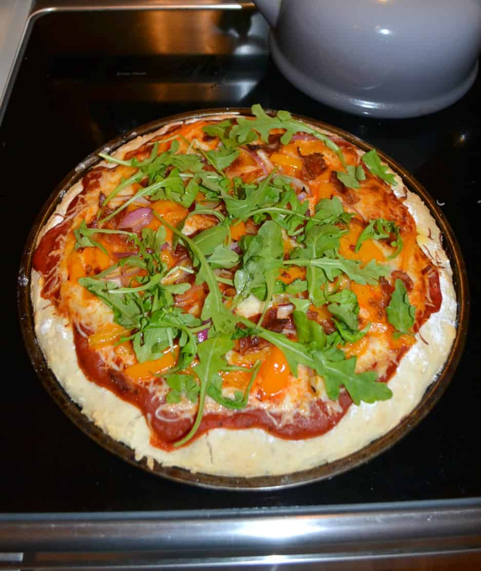 Looking for a gourmet pizza at home? Check out this Pizza topped with Bacon, Red Onions, Peppers, and Arugula
