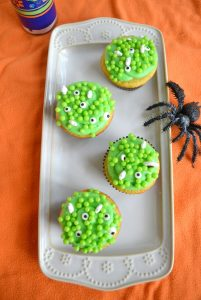 "Hocus Pocus Cupcakes are vanilla cupcakes filled with sprinkles and topped with green ""bubbles"" and eyeballs"
