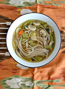 A bowl of chicken soup with soba noodles