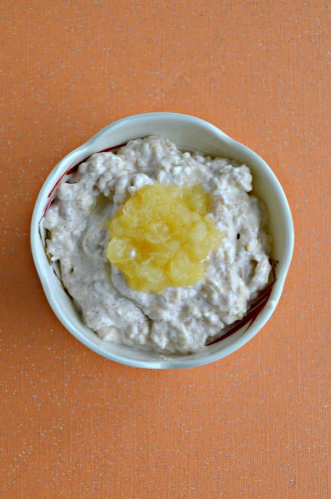 A bowl filled with cream cheese with a spoonful of rushed pineapple on top on an orange background.