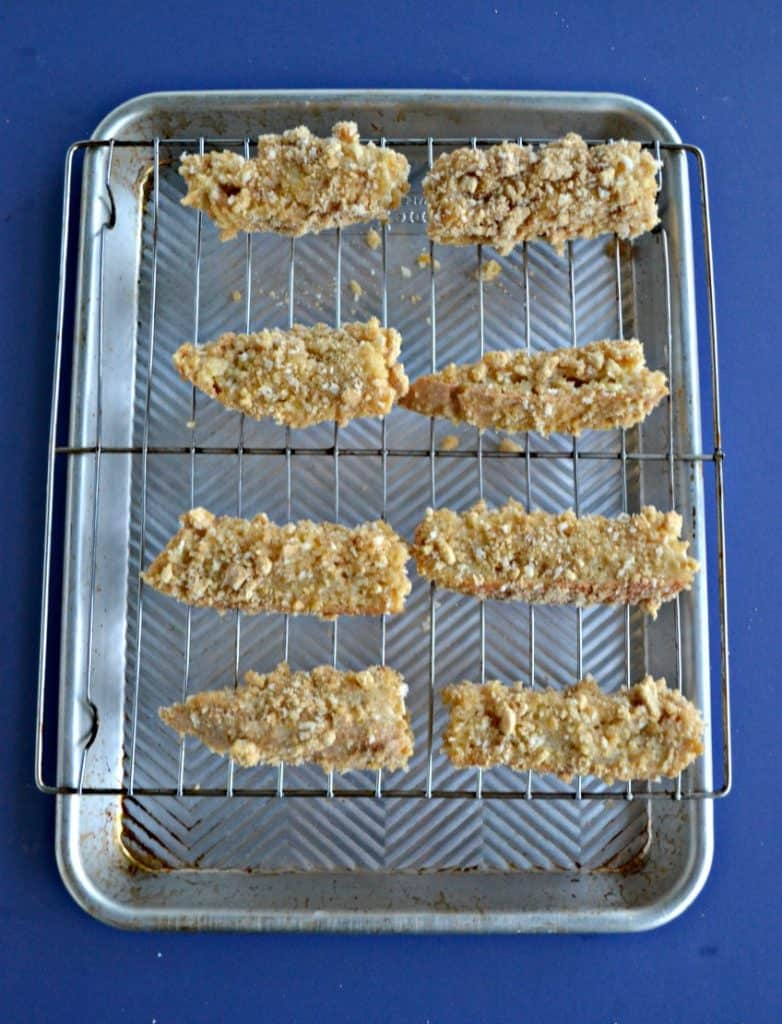 Eight french toast sticks sitting on a wire rack over top of a cookie sheet with a blue background.