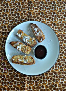 A plate with 4 French Toast sticks in a semi-circle sprinkled with powdered sugar with a cup of syrup on a cheetah background.