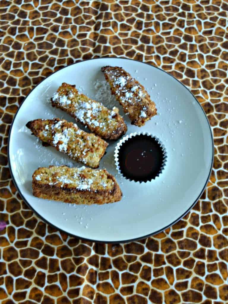 A large plate with 4 French Toast sticks in a semi-circle sprinkled with powdered sugar with a cup of syrup on a cheetah background.