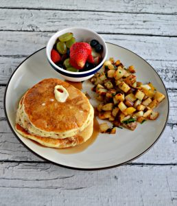 Plate with a stack of pancakes, a pile of home fries, and a small bowl of fresh fruit.