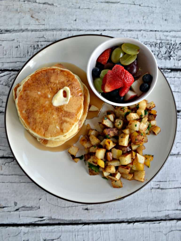 Close up of plate with a stack of pancakes, a pile of home fries, and a small bowl of fresh fruit.