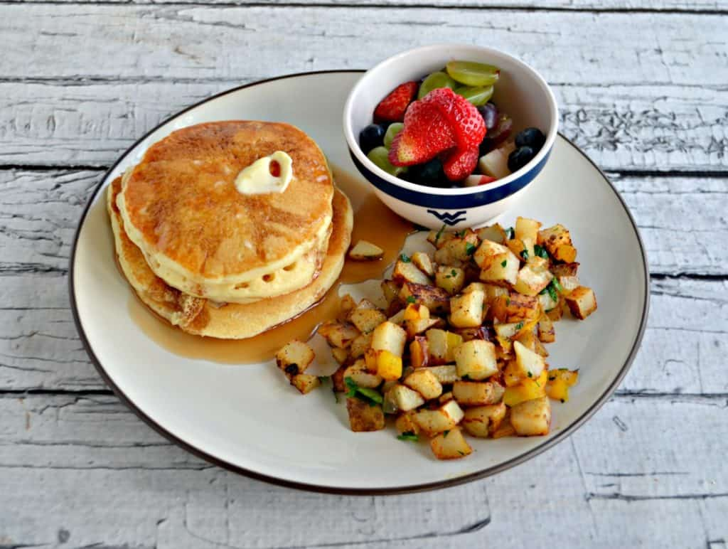 Wide angle of plate filled with a stack of pancakes, a pile of home fries, and a bowl of fruit.