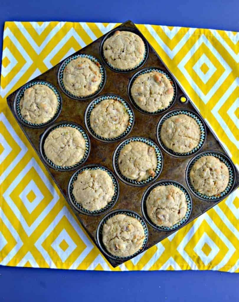 A muffin tin filled with hummingbird muffins sitting on a white and yellow placemat.