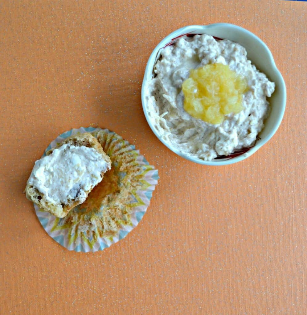 In the right upper corner is A bowl filled with cream cheese with a spoonful of rushed pineapple on top on an orange background then there is a half eaten muffin spread with the cream cheese on the lower left hand corner.