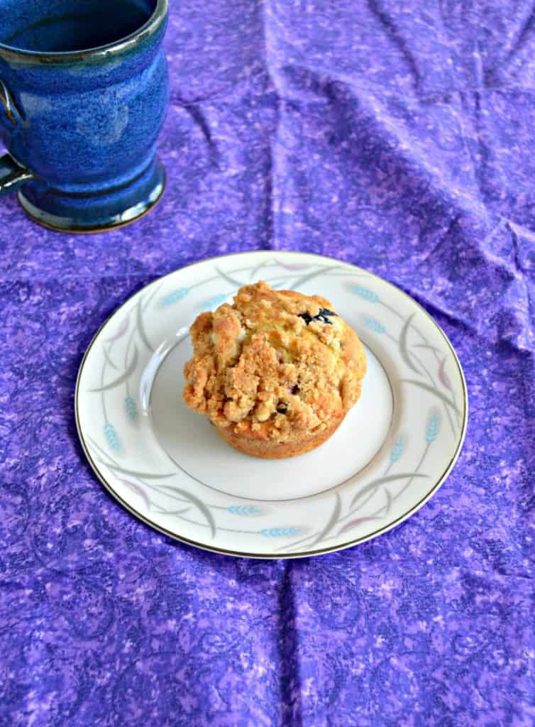 A muffin sitting on a white plate on a purple place mat with a cup of coffee in the corner.