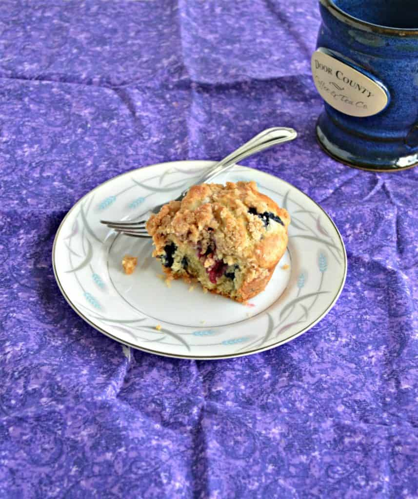 A muffin with a bite taken out of it and a fork resting next to it on a white plate on top of a purple place mat.