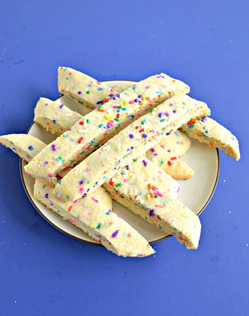 A blue background with a small plate on it topped with rainbow sprinkle biscotti