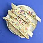 Blue background with a plate piled with rainbow sprinkle biscotti