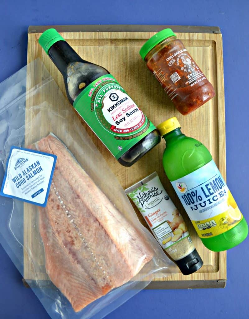 Ingredients for Korean Style BBQ Salmon on a cutting board: A large salmon filet, ssoy sauce, chile paste, ginger, lemon juice.