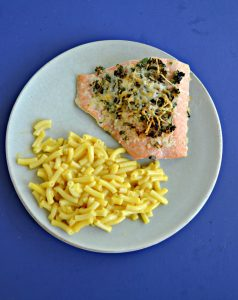 A plate with a large piece of salmon topped with herbs and a serving of macaroni and cheese with a blue background.