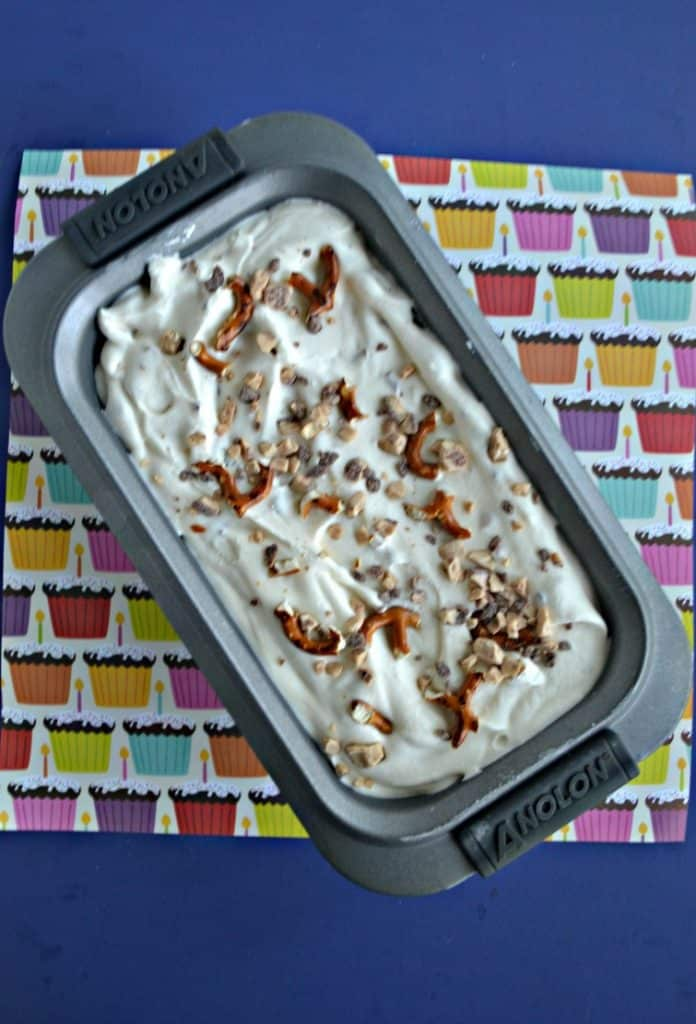 A loaf pan filled with ice cream mixture and topped with pretzel pieces and toffee chips.