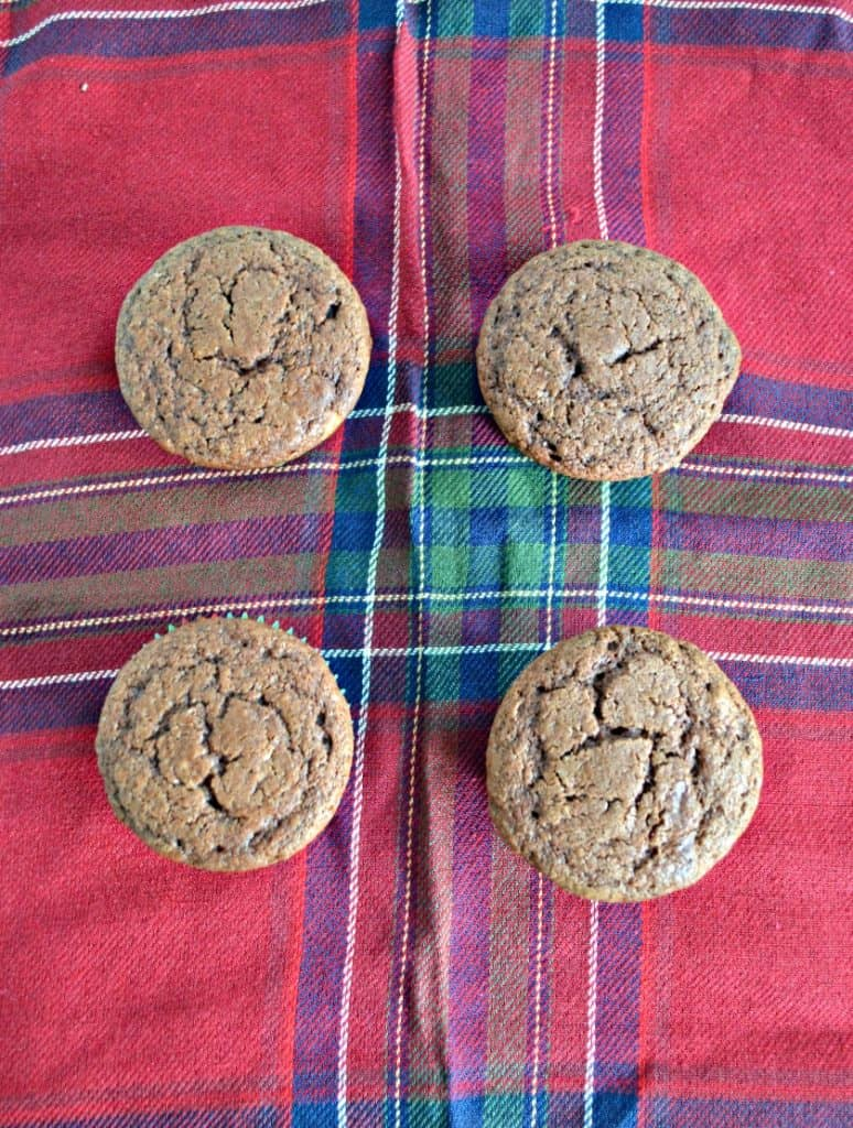 Four chocolate cupcakes sitting on a red plaid placemat