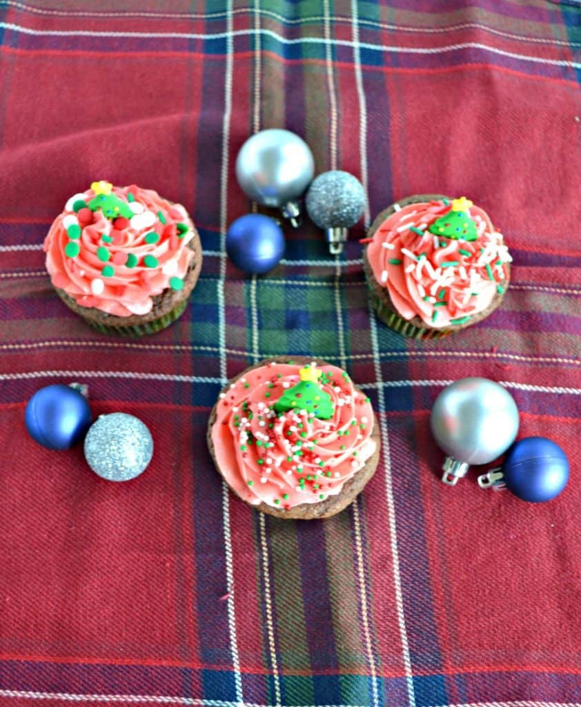 3 cupcakes with red frosting on a red plaid placemat with blue and silver ornaments