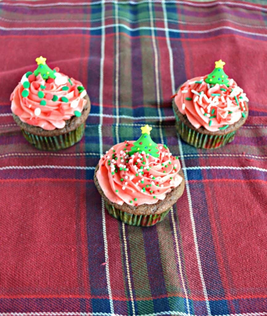 Three Cupcakes topped with red frosting and tree decorations on a red plaid placemat