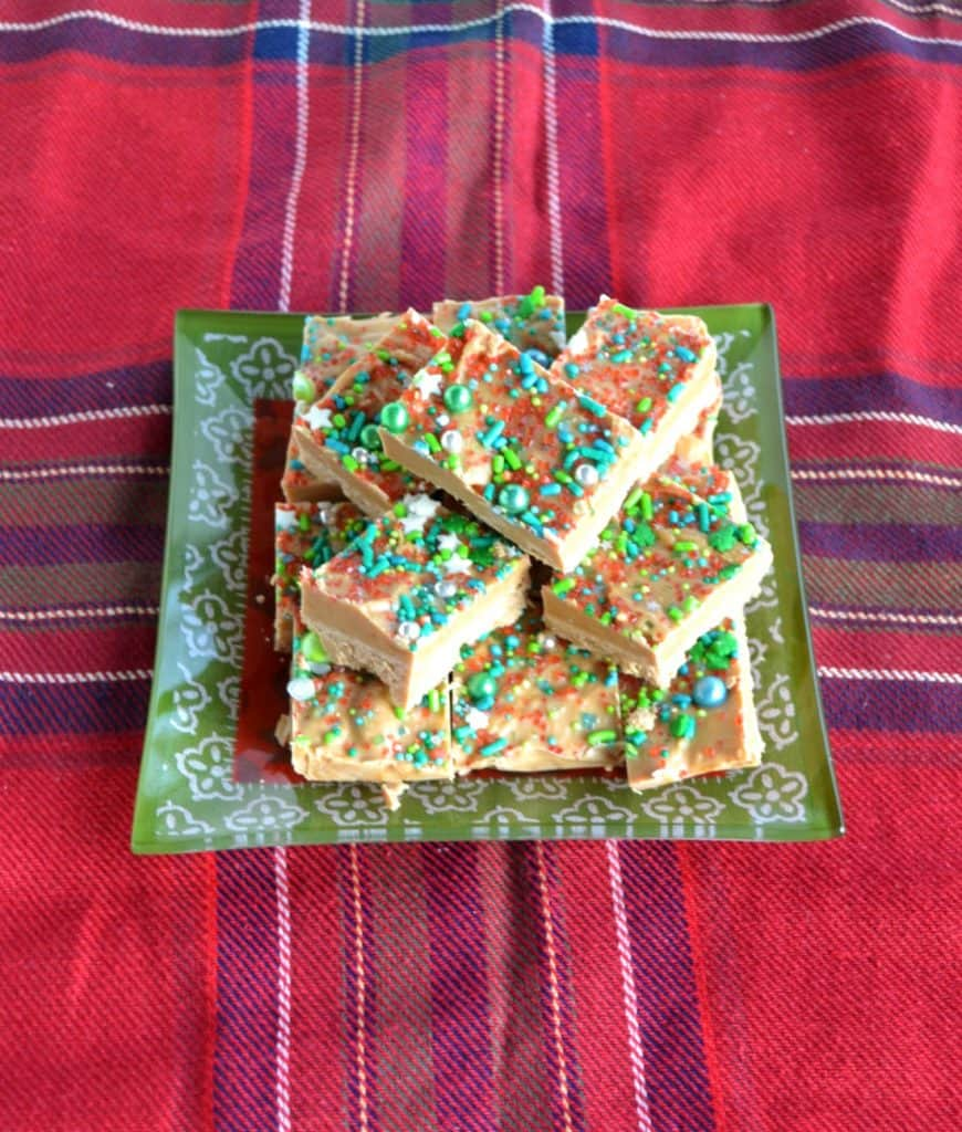 A pile of fudge on a green plate sitting on a plaid tablecloth