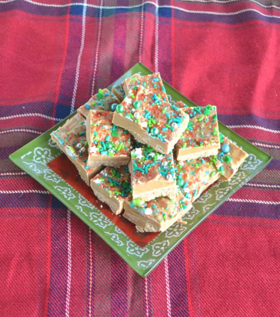 A pile of fudge on a green and red plate sitting on a red plaid tablecloth.