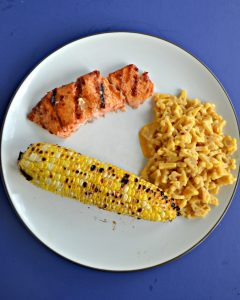 A white plate with an ear of grilled corn, a spoonful of macaroni and cheese, and a grilled salmon filet.