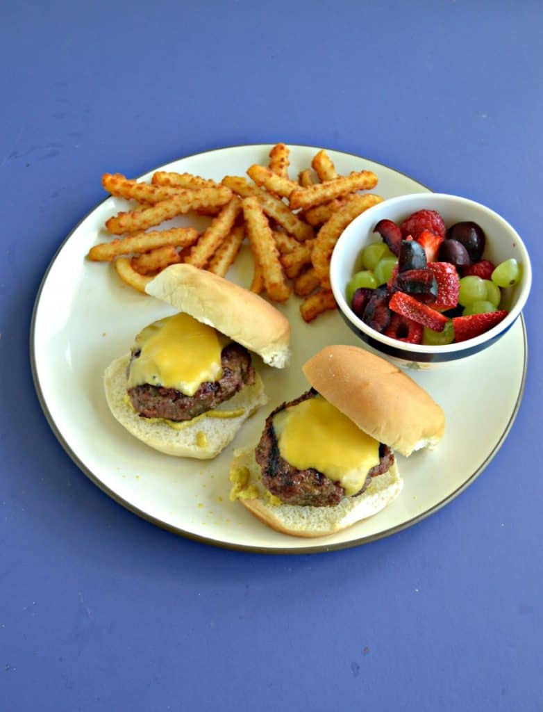 Top view of a plate with two burger sliders, a handful of fries, and a cup of mixed fruit on a blue background,