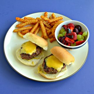 A plate with two cheeseburger sliders, a handful of fries, and a bowl of mixed fruit and berries on a blue background.