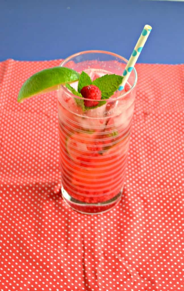 Raspberry Mojito in a tall glass garnished with a raspberry and mint sprig with a paper straw.