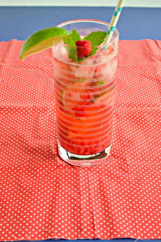 Raspberry Mojito in a tall glass filled with ice garnished with a raspberry and mint sprig with a paper straw.