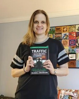 Blog owner holding a copy of the Traffic secrets book.