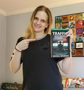 Blog owner pointing at a copy of the book Traffic secrets in her other hand.