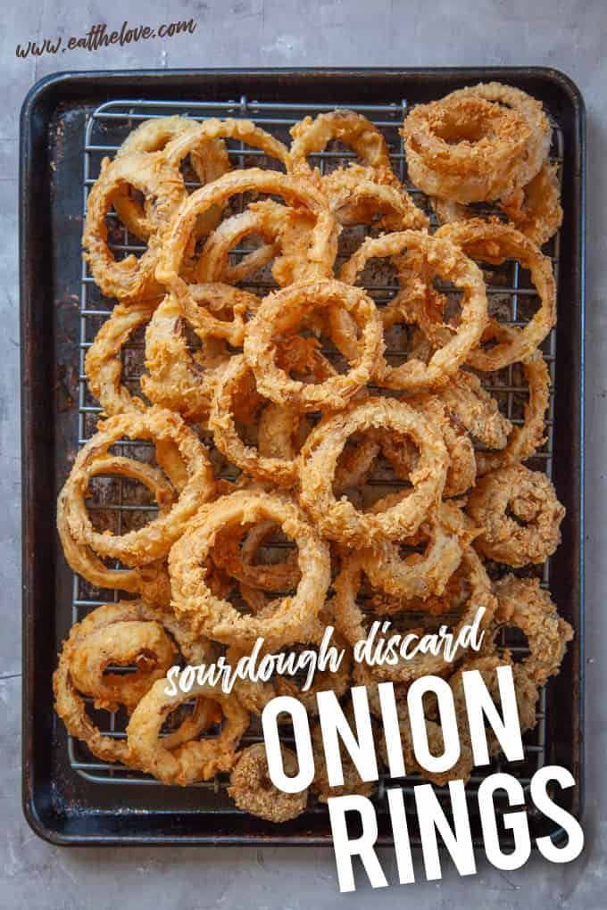 A sheet pan piled with sourdough onion rings.