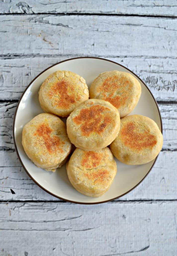 A white plate topped with 6 golden brown English Muffins