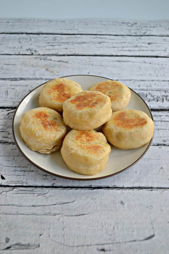 Side view of A white plate topped with 6 golden brown English Muffins