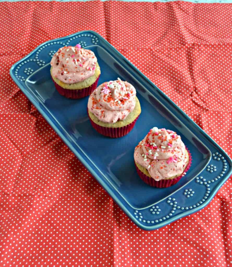 3 cupcakes topped with pink frosting sitting on a blue platter on a red backdrop.