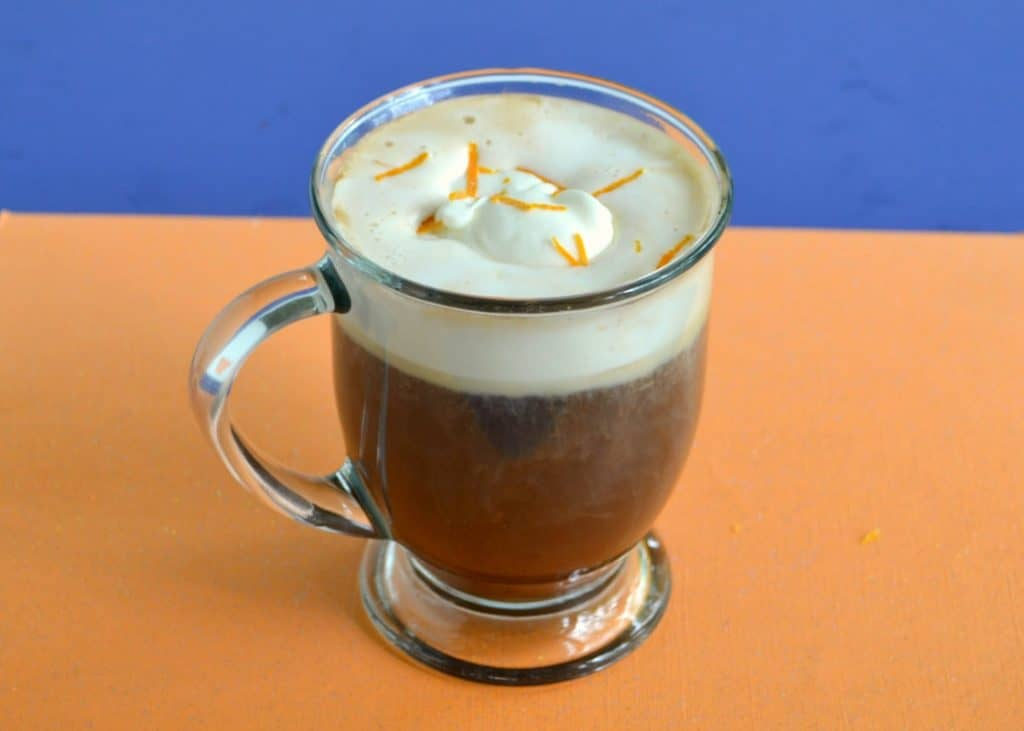 A clear coffee mug with coffee on the bottom two thirds and whipped cream on the top with orange zest on top.