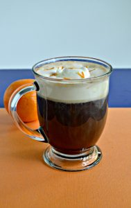 A clear coffee mug with coffee on the bottom two thirds and whipped cream on the top with orange zest on top and an orange in the background on a blue and orange background.